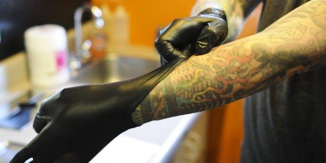 Tatuador usando guantes desechables